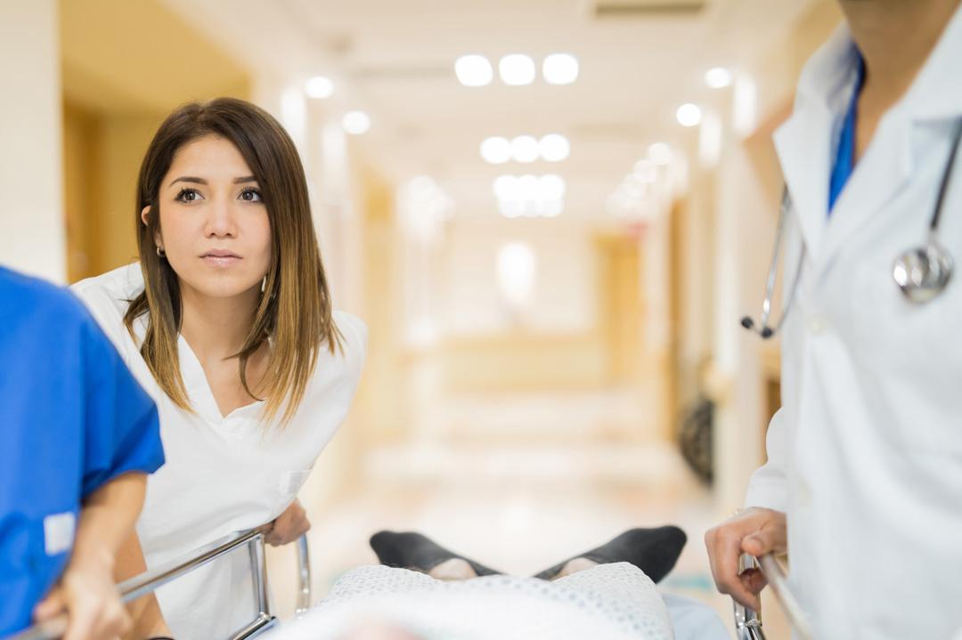 Krankenschwester schiebt Bett
