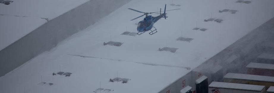 Hubschrauber über schneebedecktem Dach