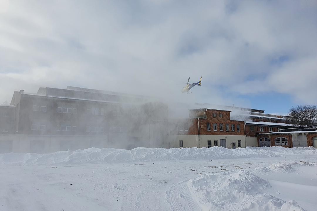 Helikopter über schneebedecktem Dach