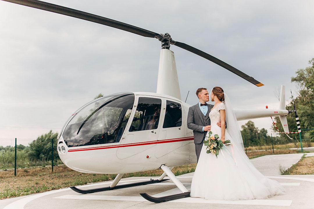 Brautpaar vor einem Helikopter
