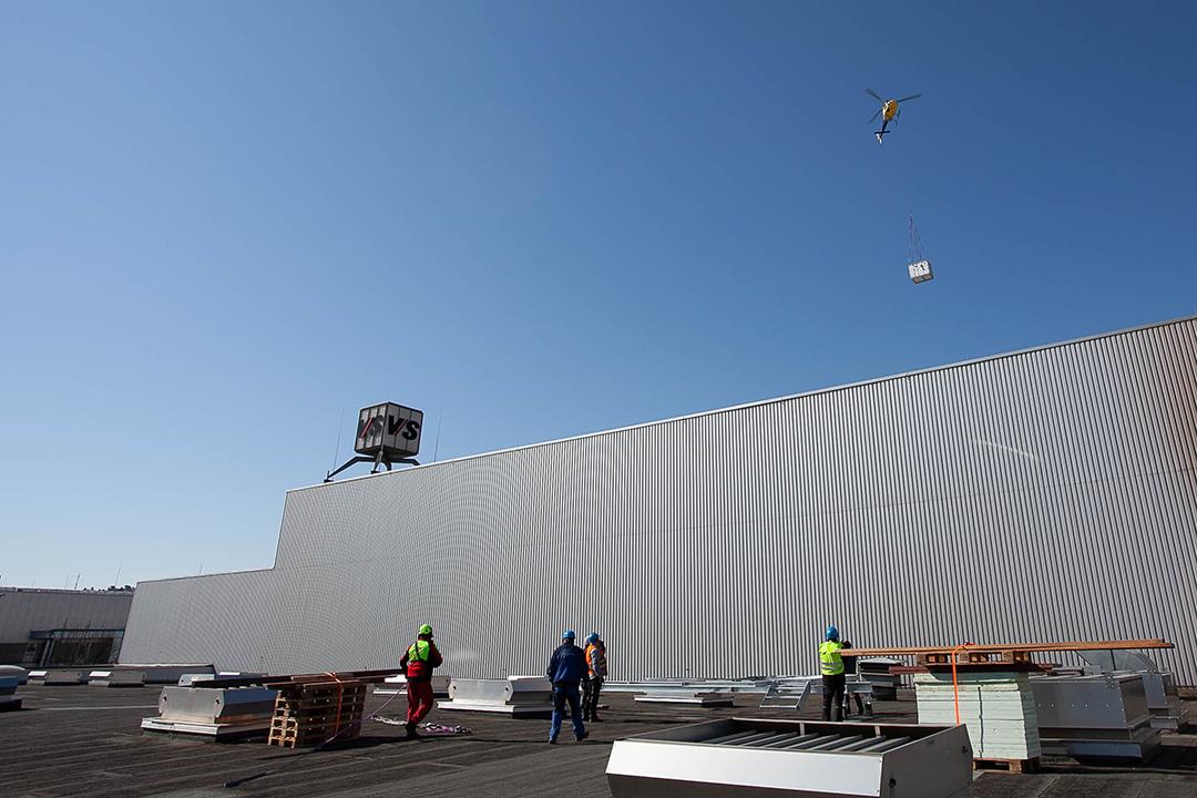 Lastenhubschrauber mit Klimagerät über Werkshalle